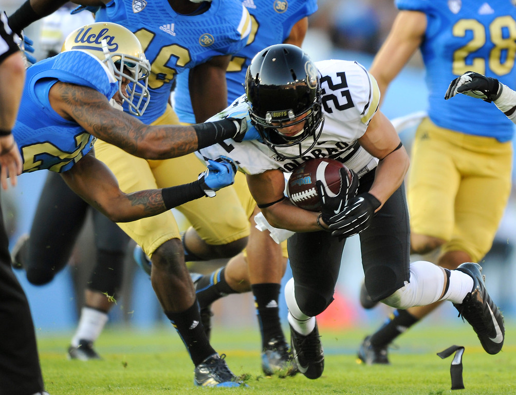 . Colorado\'s Nelson Spruce, of Westlake High School, is taken down by UCLA\'s Brandon Sermons who was called for a facemasking penalty, Saturday, November 2, 2013, at the Rose Bowl. (Photo by Michael Owen Baker/L.A. Daily News)