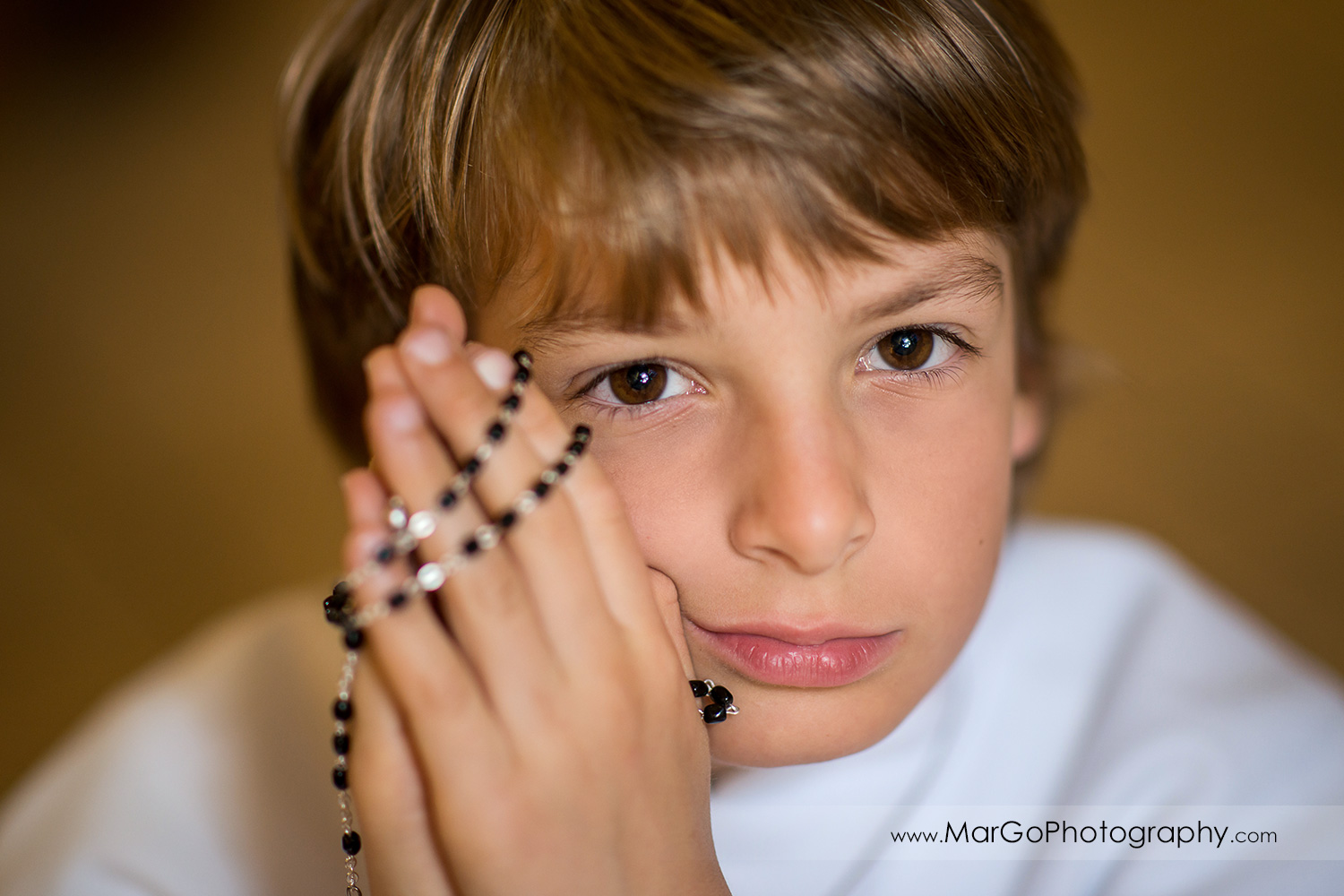 first communion boy in white alb holding rosary in wooden San Jose church pews