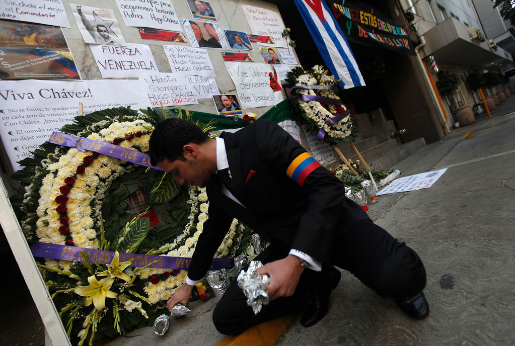 . An employee of Venezuela\'s embassy arranges candles in front flowers and signs left outside the embassy in remembrance of Venezuela\'s late President Hugo Chavez in Mexico City March 6, 2013.  REUTERS/Edgard Garrido