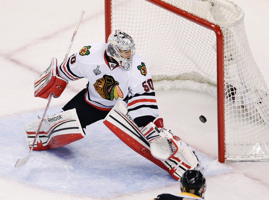 . The puck, shot by Boston Bruins center Rich Peverley, not seen, finds the net behind Chicago Blackhawks goalie Corey Crawford (50) for a goal during the first period in Game 4 of the NHL hockey Stanley Cup Finals, Wednesday, June 19, 2013, in Boston. (AP Photo/Charles Krupa)