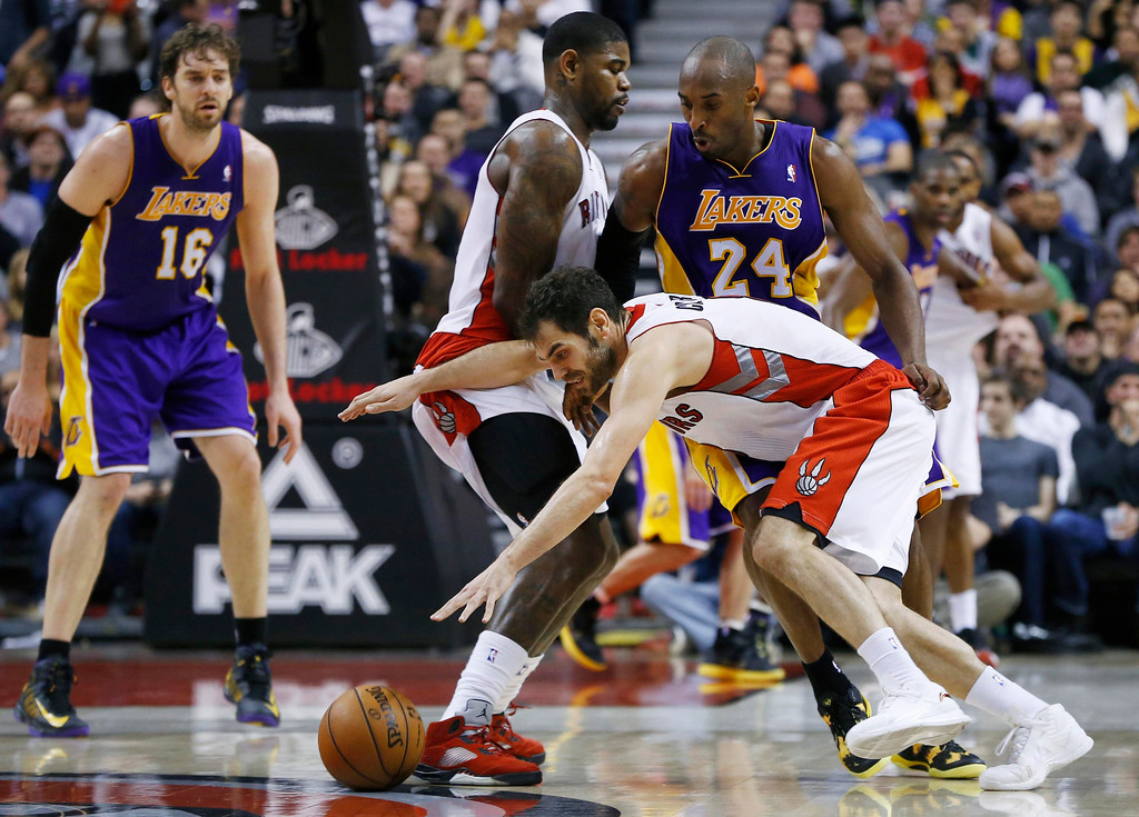 . Toronto Raptors\' Jose Calderon (bottom R) drives as teammate Amir Johnson (C) sets a pick on Los Angeles Lakers\' Kobe Bryant (24) during the second half of their NBA basketball game in Toronto, January 20, 2013.     REUTERS/Mark Blinch