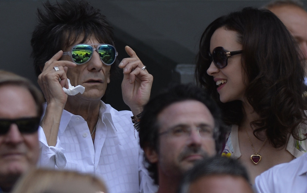 . British musician Ronnie Wood of The Rolling Stones (L) sits with his wife Sally Humpheys in the crowd watching the men\'s singles final between Serbia\'s Novak Djokovic and Britain\'s Andy Murray on day thirteen of the 2013 Wimbledon Championships tennis tournament at the All England Club in Wimbledon, southwest London, on July 7, 2013.  ADRIAN DENNIS/AFP/Getty Images