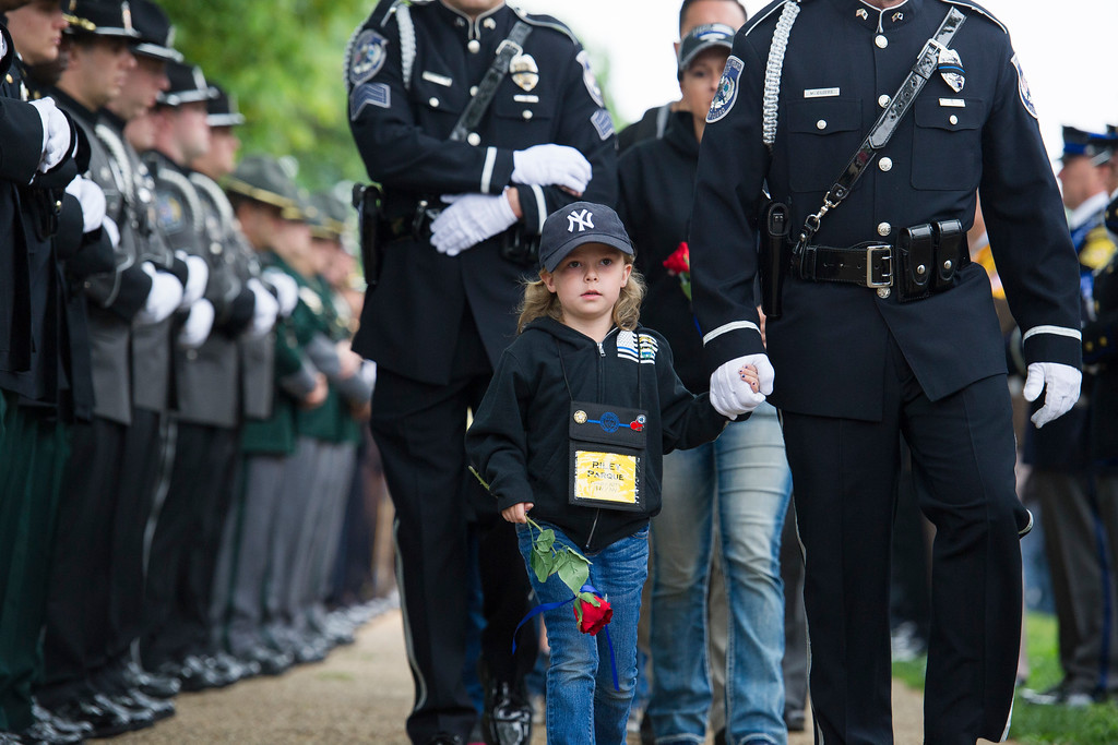 . Five year-old Riley Parque holds the hand of a police officer as her family arrives for the National Law Enforcement Officers Memorial Fund 30th annual Candlelight Vigil, to commemorate new names added to the monument, on the Mall in Washington, Sunday, May 13, 2018. Riley\'s father, a police officer, Chad Parque, of the North Las Vegas Police Department, died in the line of duty Jan. 1, 2017. (AP Photo/Cliff Owen)