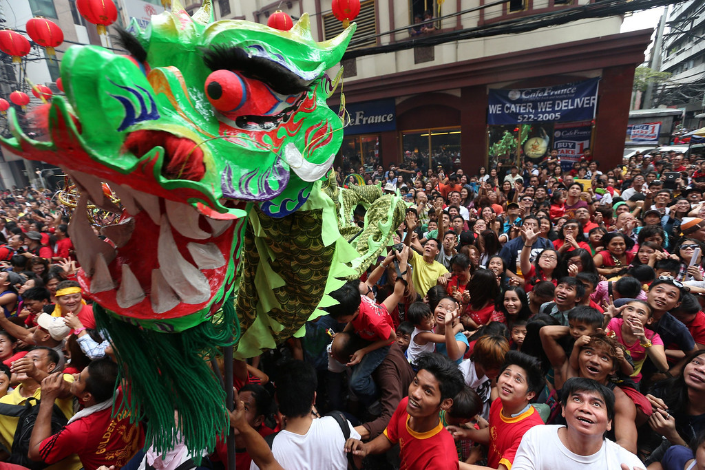 . Performers carry a dragon figure while Filipinos try to catch candies and coins  thrown by store workers from a balcony  s they mark the Chinese New Year in  Binondo Chinatown district of Manila, Philippines, 31 January 2014.   EPA/DENNIS M. SABANGAN