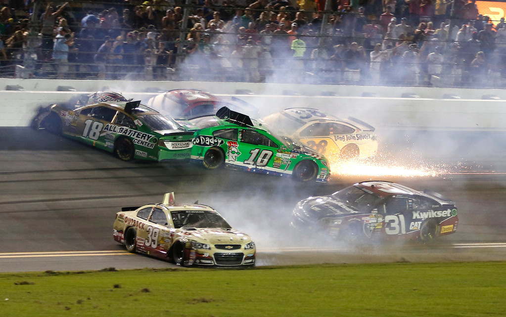 . Cars wreck on the front stretch including Kyle Busch (18), Danica Patrick (10), Ryan Newman (39),  David Gilliland (38), and Jeff Burton (31) on the last lap of the NASCAR Sprint Cup auto race at Daytona International Speedway, Saturday, July 6, 2013, in Daytona Beach, Fla. (AP Photo/Reinhold Matay)