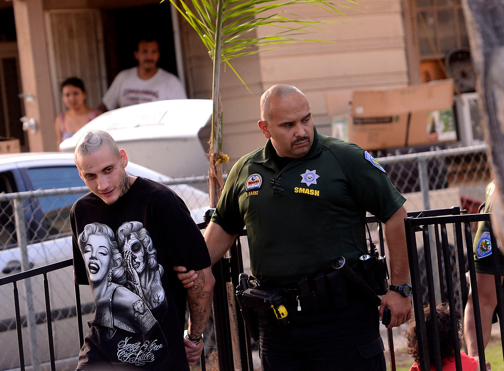 . San Bernardino Police officer Serbando Saenz arrests a man for parole violations along the 200 block of Tenth Street as seen during a county wide police sweep in San Bernardino August 2, 2013. GABRIEL LUIS ACOSTA/STAFF PHOTOGRAPHER.