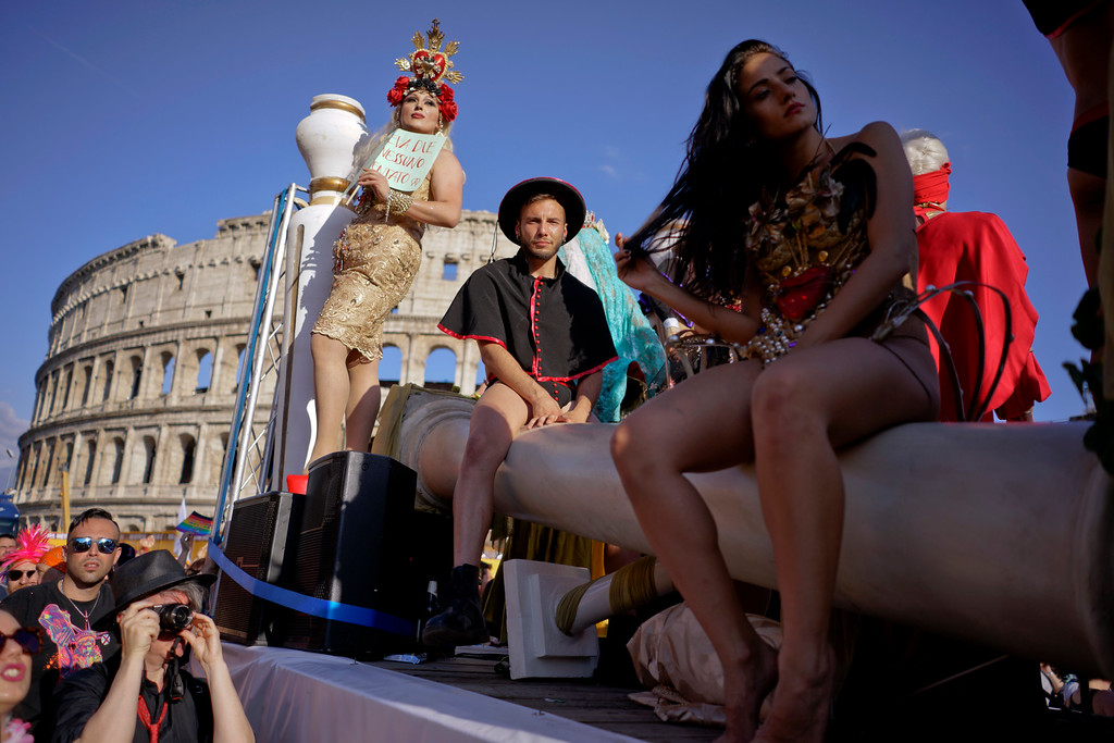. People take part in the annual Gay Pride parade as the Colosseum is visible in background, in Rome, Saturday, June 9, 2018. (AP Photo/Andrew Medichini)