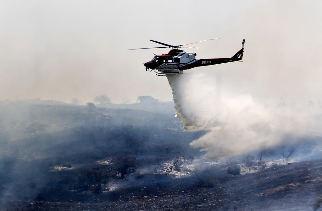 . A helicopter attacks a wildfire burning in the north county of San Diego Tuesday, May 13, 2014, in San Diego. Wildfires pushed by gusty winds chewed through canyons parched by California\'s drought, prompting evacuation orders for more than 20,000 homes on the outskirts of San Diego and another 1,200 homes and businesses in Santa Barbara County 250 miles to the north. (AP Photo)