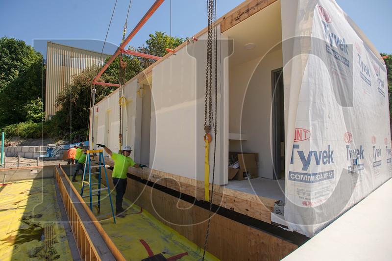 Cody Humphrey helps guide a modular unit into place atop a foundation. (Josh Kulla/DJC)