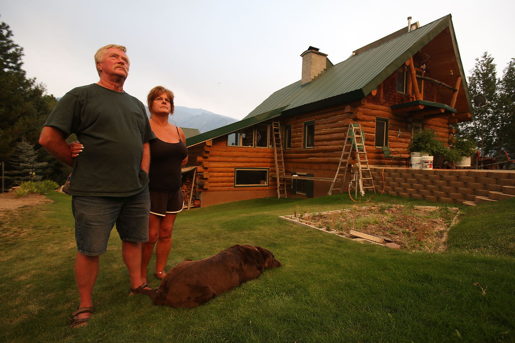 . John and Cindy Larson watch flames on the ridge behind their house as firefighters worked to build a defensive line around their neighborhood to protect them from more than 90,000-acre Elk Complex Fire near Pine, Idaho, on Monday, Aug. 12, 2013.   (AP Photo/Times-News, Ashley Smith) MANDATORY CREDIT