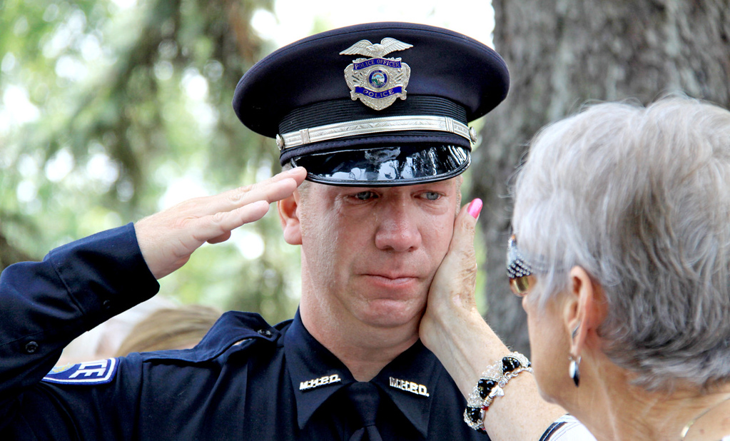 . Mendota Heights police officer John Larrive is comforted by a friend oustide St. Stephen\'s Lutheran Church following the funeral service for officer Scott Patrick in West St. Paul on Wednesday. (Minnesota Department of Public Safety Pool Photo: Jen Longaecker)