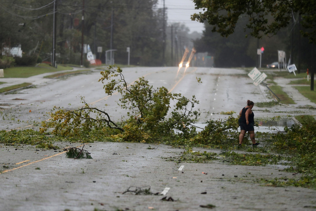 . A woman removes debris from a road in Wilmington, N.C., after Hurricane Florence made landfall Friday, Sept. 14, 2018. (AP Photo/Chuck Burton)