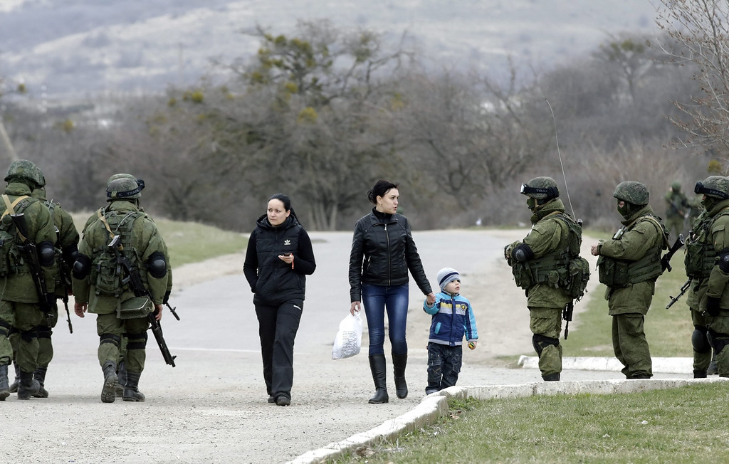 . A local young woman speaks with armed men in military uniform who stand outside the territory of a Ukrainian military unit in the village of Perevalnoye, outside Simferopol, Ukraine, 04 March 2014.  EPA/MAXIM SHIPENKOV