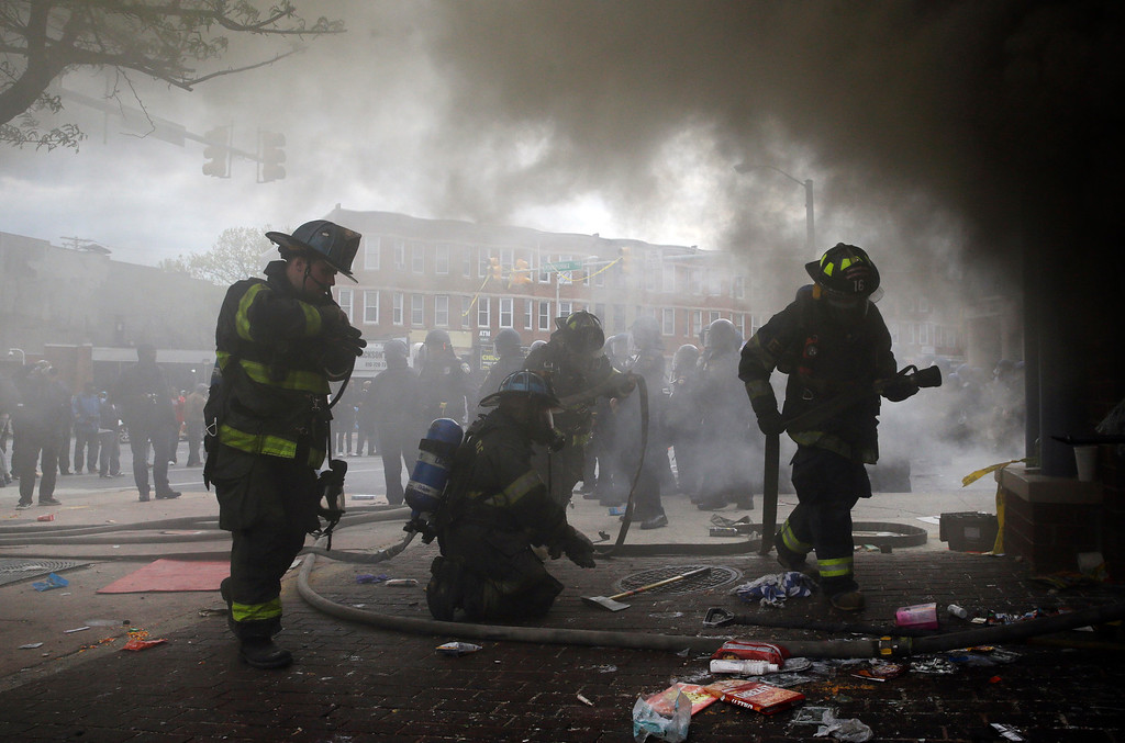. Firefighters prepare to put out a fire at a store, Monday, April 27, 2015, during unrest following the funeral of Freddie Gray in Baltimore. Gray died from spinal injuries about a week after he was arrested and transported in a Baltimore Police Department van. (AP Photo/Patrick Semansky)