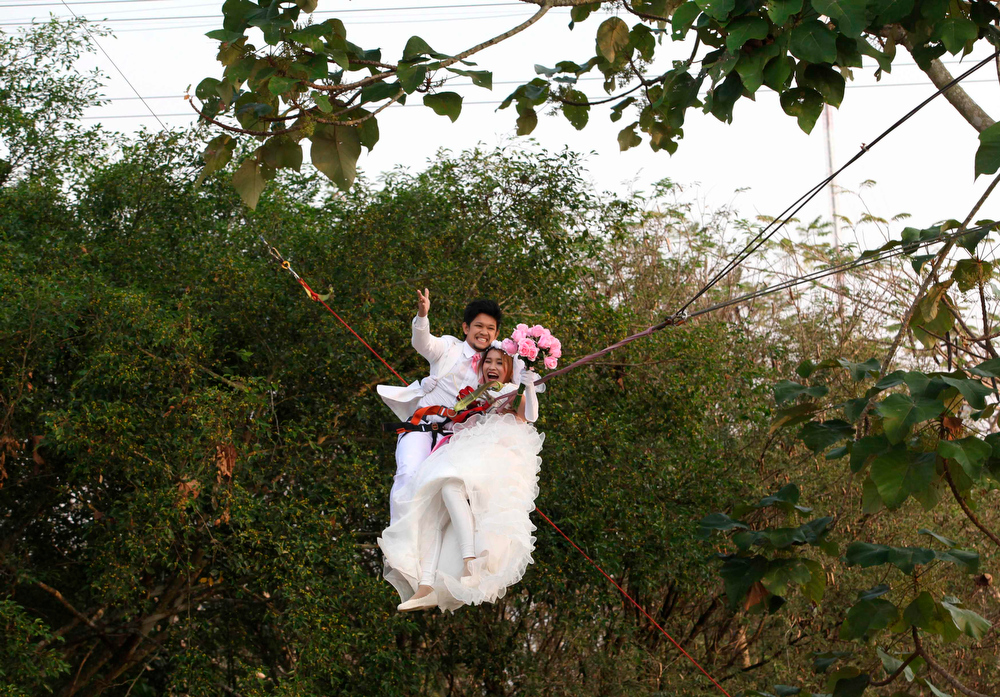 . Thai groom Prasit Rangsiyawong (L), 29, and his bride Varuttaon Rangsiyawong, 27, fly while attached to cables during a wedding ceremony ahead of Valentine\'s Day in Prachin Buri province, east of Bangkok February 13, 2013. Three Thai couples took part in the wedding ceremony arranged by a Thai resort that aimed to strengthen the relationships of the couples by doing fun activities.  REUTERS/Kerek Wongsa)