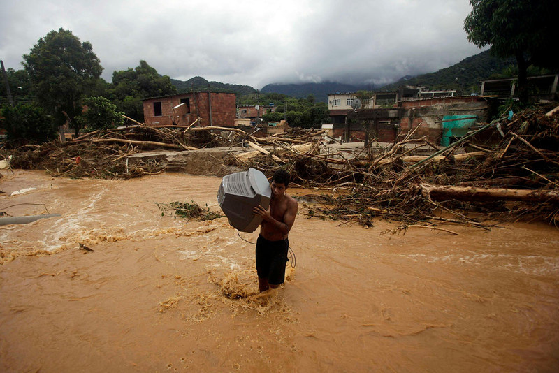 ". REFILE - CORRECTING TYPO IN ""CAPIVARI\"" A man carries a television set as he crosses the Capivari river in Xerem, in Duque de Caxias near Rio de Janeiro January 3, 2013. At least 255 people were dislodged and one person died during the floods of Capivari River in Xerem, a district of Duque de Caxias, local media said. REUTERS/Ricardo Moraes (BRAZIL - Tags: ENVIRONMENT DISASTER SOCIETY TPX IMAGES OF THE DAY)"