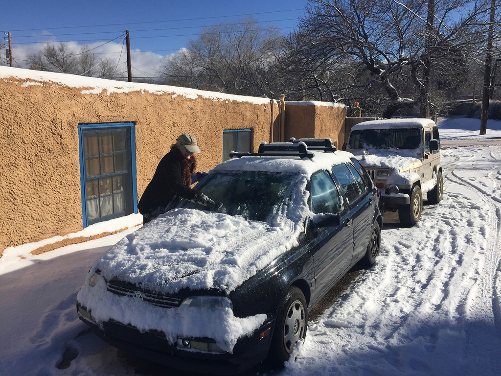 . Peggy Blitz, 76, of Santa Fe, N.M., clears her windshield of ice as residents dig out from a winter storm that closed schools and blanketed nearby ski resorts with snow on Friday, Jan. 6, 2017. Authorities reported difficult driving conditions on on the state\'s two main interstate highways. (AP Photo/Morgan Lee)
