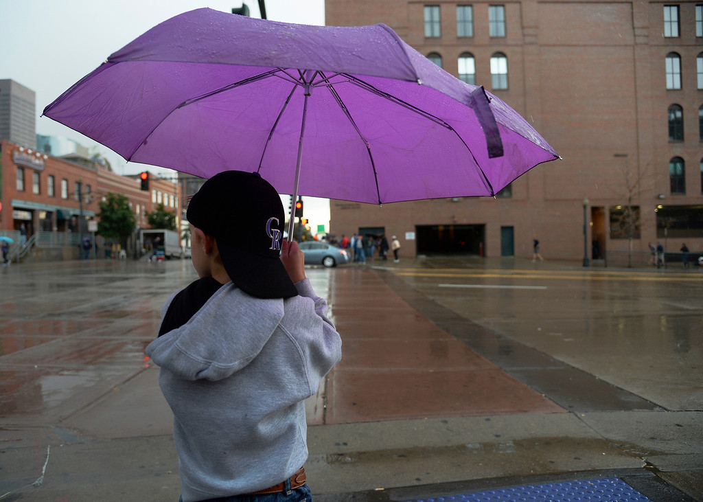 . Logan Christensen, 5, of Ft. Lupton, takes cover under an umbrella while waiting to cross the street after leaving the stadium to take cover from the rain prior to the Colorado Rockies/Los Angeles Dodgers baseball game on Sunday, June 8, 2014 at Coors Field. (Photo by John Leyba/The Denver Post)