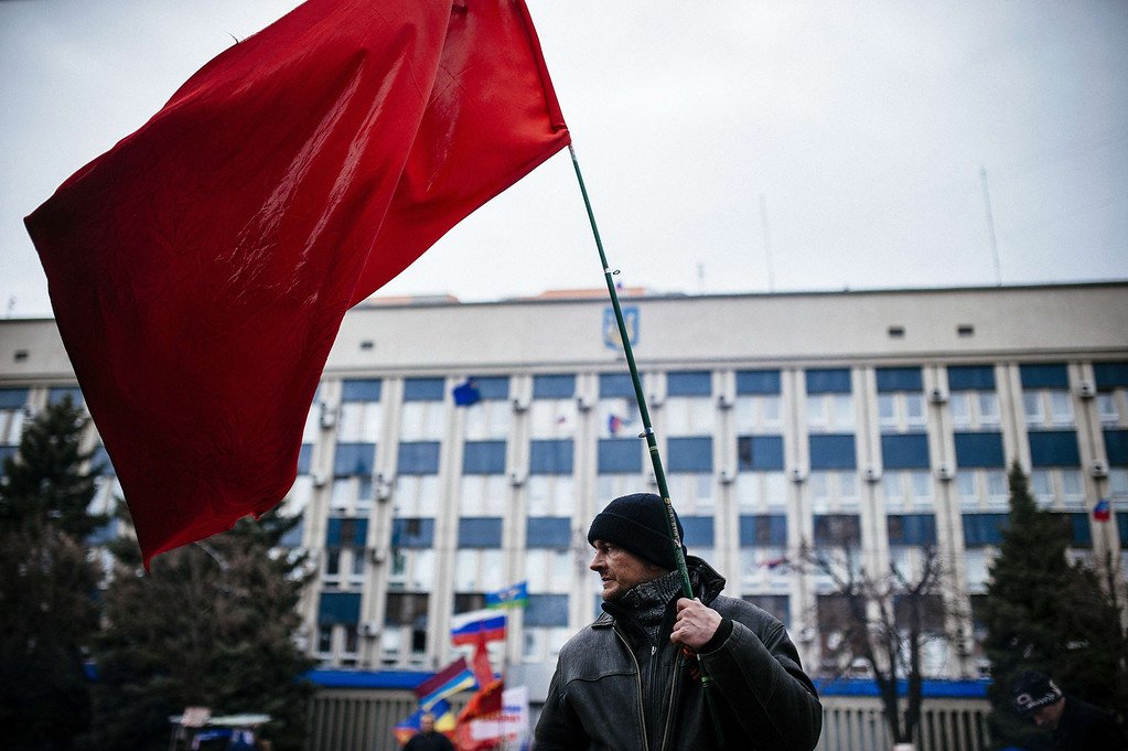 . A Pro-Russian activist holds a Soviet Union flag outside the headquarters of Ukraine\'s security agency in the eastern Ukrainian city of Lugansk on April 13, 2014. Ukraine\'s interior minister said on April 13 that both sides had suffered casualties during a raid launched by Ukrainian special forces on a police station in the eastern city of Slavyansk that was seized by pro-Russian gunmen. AFP PHOTO / DIMITAR DILKOFF