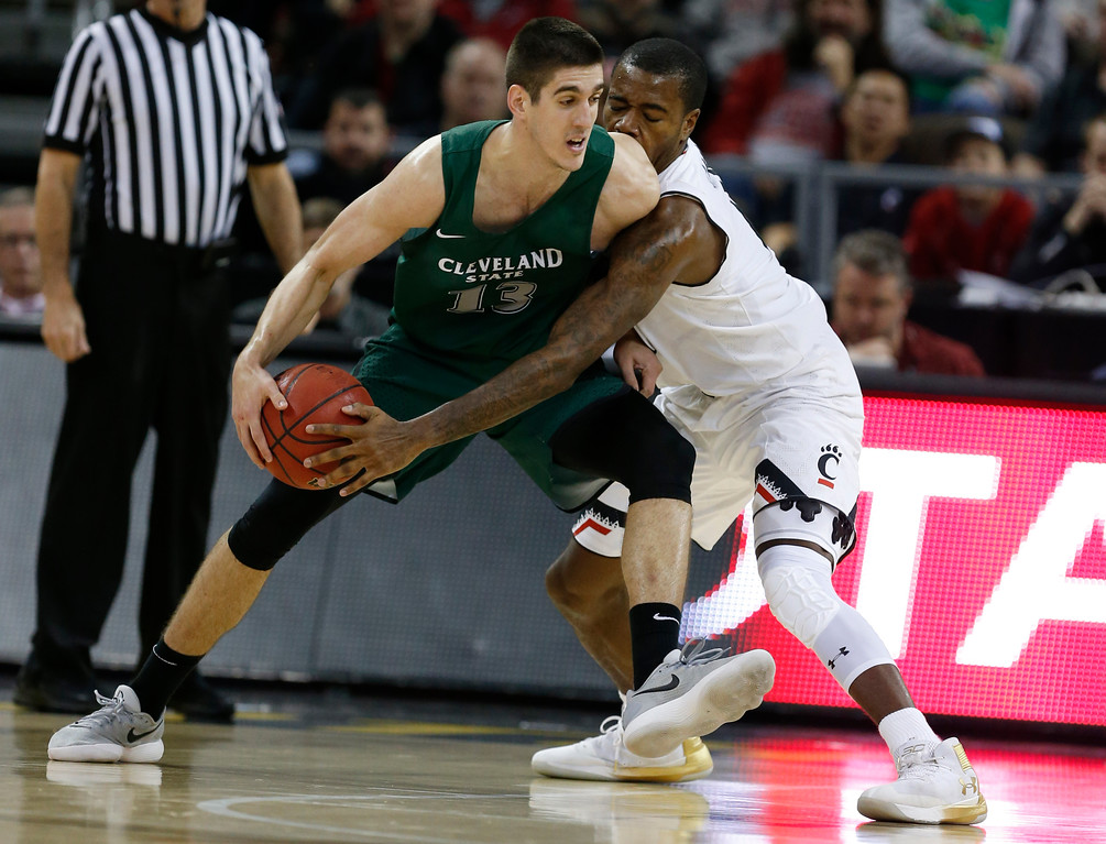 . Cincinnati guard Jacob Evans, right, pressures Cleveland State forward Stefan Kenic (13) during the second half of an NCAA college basketball game Thursday, Dec. 21, 2017, in Highland Heights, Ky. Cincinnati won 81-62. (AP Photo/Gary Landers)