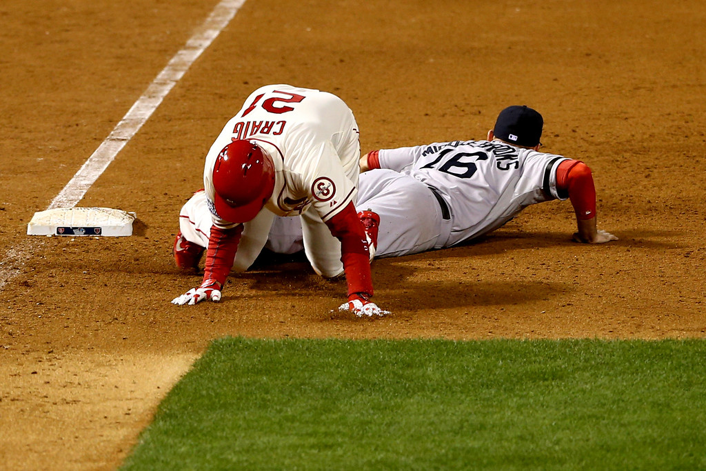 . ST LOUIS, MO - OCTOBER 26:  Allen Craig #21 of the St. Louis Cardinals gets tripped up by Will Middlebrooks #16 of the Boston Red Sox during the ninth inning of Game Three of the 2013 World Series at Busch Stadium on October 26, 2013 in St Louis, Missouri.  (Photo by Elsa/Getty Images)