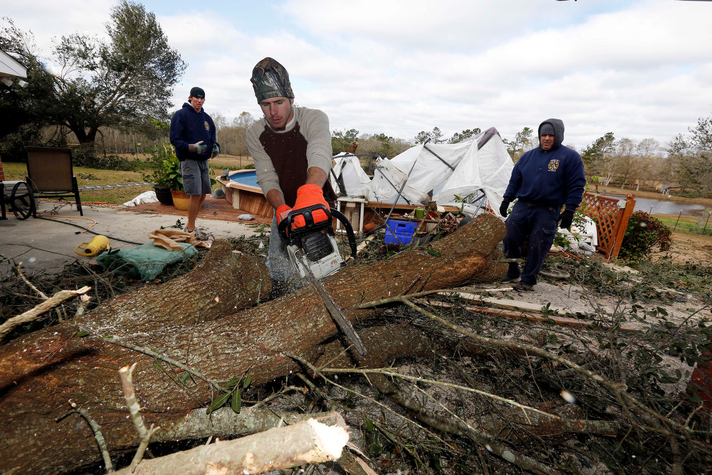 . Kevin Briggs cuts into a downed tree as friends wait to remove the wood as cleanup continues at his father-in-law\'s home in McNeill, Miss., Wednesday, Dec. 26, 2012. The Christmas storm destroyed Daryl Keene\'s barn, workshop, part of his roof and home and felled most of the oak trees on the property. More than 25 people were injured and at least 70 homes were damaged in Mississippi by the severe storms that pushed across the South on Christmas Day, authorities said Wednesday. Damages have been reported in 10 counties and officials continue to assess the situation. (AP Photo/Rogelio V. Solis)