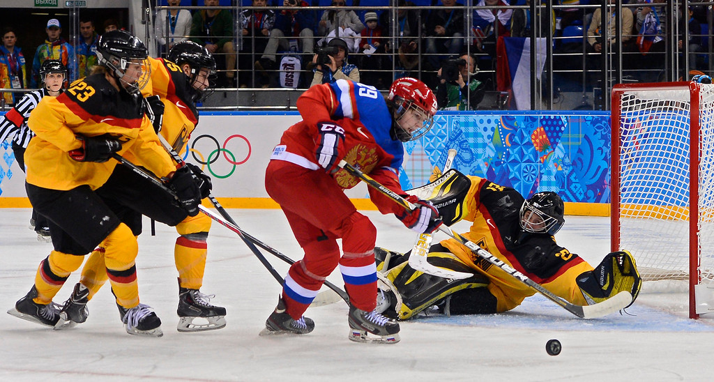 . Anna Shokhina (C) of Russia takes a shot against goalie Viona Harrer (R) of Germany in the first period during the women\'s match between Russia and Germany at the Shayba Arena in the Ice Hockey tournament at the Sochi 2014 Olympic Games, Sochi, Russia, 09 February 2014.  EPA/LARRY SMITH