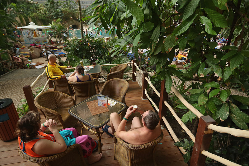 . A visitors enjoys an ice cream near the lagoon at the Tropical Islands indoor resort on February 15, 2013 in Krausnick, Germany. Located on the site of a former Soviet military air base, the resort occupies a hangar built originally to house airships designed to haul long-distance cargo. Tropical Islands opened to the public in 2004 and offers visitors a tropical getaway complete with exotic flora and fauna, a beach, lagoon, restaurants, water slide, evening shows, sauna, adventure park and overnights stays ranging from rudimentary to luxury. The hangar, which is 360 metres long, 210 metres wide and 107 metres high, is tall enough to enclose the Statue of Liberty.  (Photo by Sean Gallup/Getty Images)