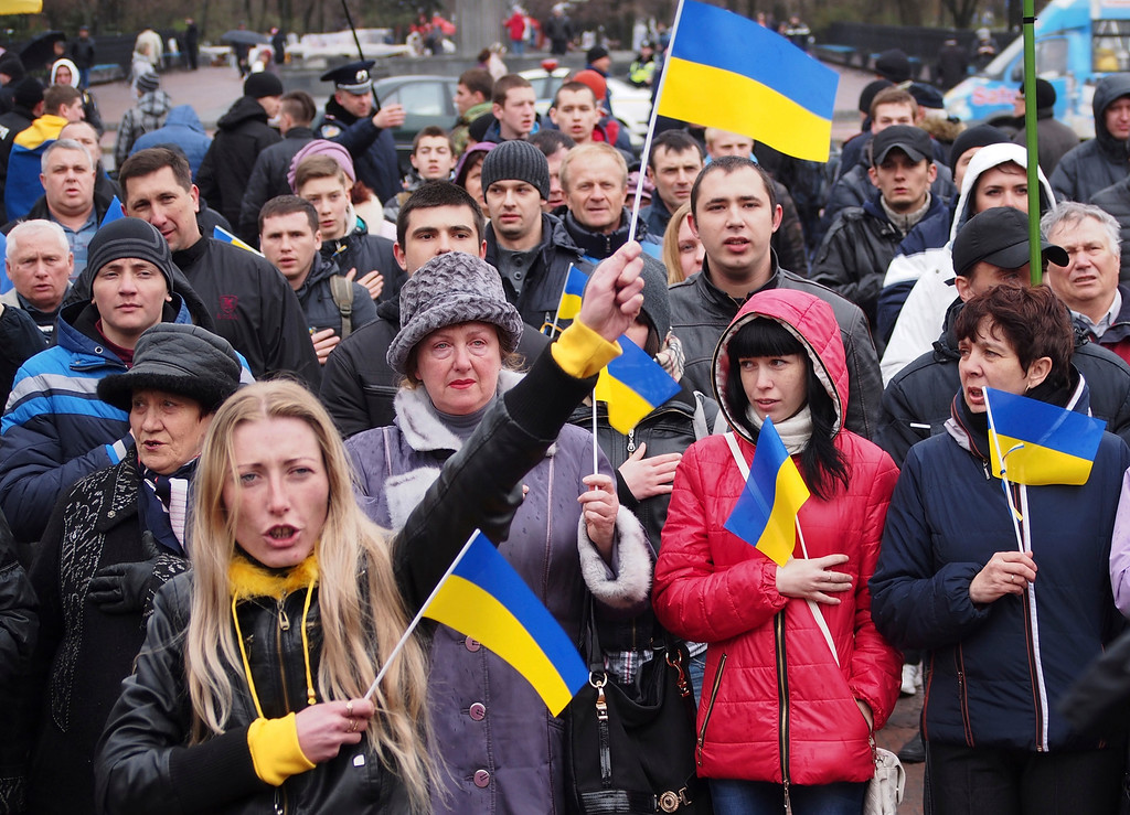 """. Demonstrators wave Ukrainian national flags during a pro-Ukraine rally in Luhansk, 30 kilometers (20 miles) west of the Russian border, Ukraine, Sunday, April 13, 2014. Ukraine is launching a \""""large-scale anti-terrorist operation\"""" to resist attacks of armed pro-Russian forces, Ukraine\'s President Oleksandr Turchynov said on Sunday in a televised address.(AP Photo/Igor Golovniov)"""