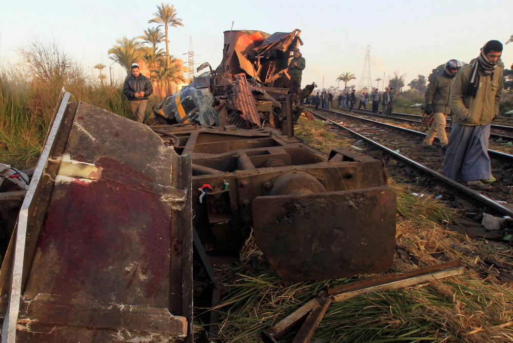. Men walk beside the wreckage of a military train crash in the Giza neighbourhood of Badrashin, about 40 km (25 miles) west of Cairo, January 15, 2013. A military train carrying young recruits to an army camp derailed in a Cairo suburb on Tuesday, killing 19 people and injuring 107, Egypt\'s health ministry spokesman said. REUTERS/Mohamed Abd El Ghany