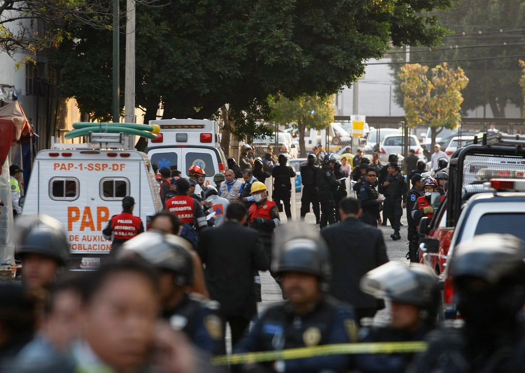 . Ambulances and rescue personnel are seen on a street outside the headquarters of state oil giant Pemex in Mexico City January 31, 2013. A powerful explosion rocked the Mexico City headquarters of Pemex on Thursday, killing at least 14 people and injuring 100 others.    REUTERS/Bernardo Montoya
