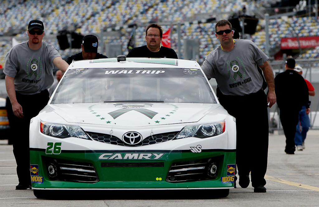 . DAYTONA BEACH, FL - FEBRUARY 20:  Crew members push the Michael Waltrip, driver of the #26 Sandy Hook School Support Fund Toyota, through the garage area during practice for the NASCAR Sprint Cup Series Daytona 500 at Daytona International Speedway on February 20, 2013 in Daytona Beach, Florida.  (Photo by Jonathan Ferrey/Getty Images)
