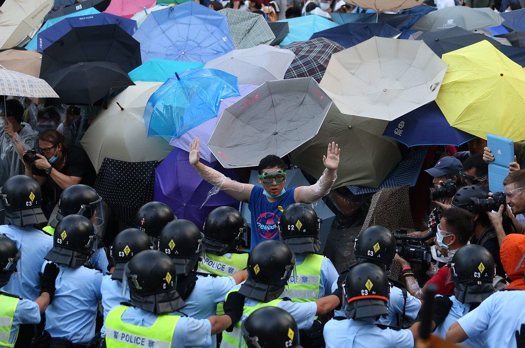 . A pro-democracy demonstrator (C) gestures in front of a police line near the Hong Kong government headquarters on September 28, 2014. Police fired tear gas as tens of thousands of pro-democracy demonstrators brought parts of central Hong Kong to a standstill Sunday, in a dramatic escalation of protests that have gripped the semi-autonomous Chinese city for days. AFP PHOTO / AARON TAM