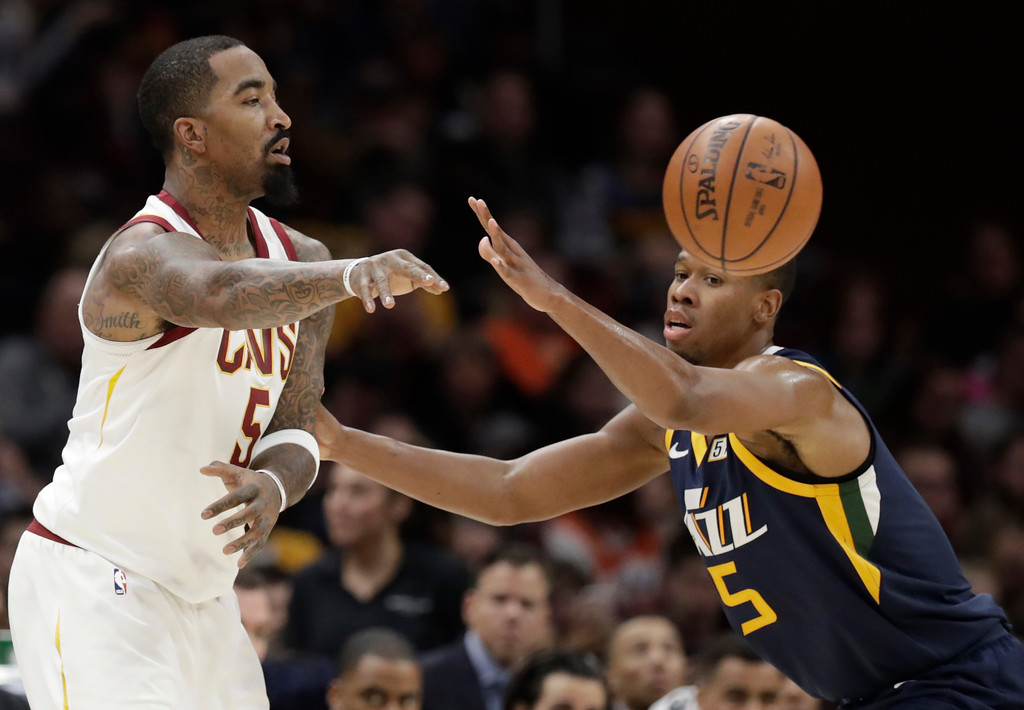 . Cleveland Cavaliers\' JR Smith, left, passes against Utah Jazz\'s Rodney Hood in the first half of an NBA basketball game, Saturday, Dec. 16, 2017, in Cleveland. (AP Photo/Tony Dejak)