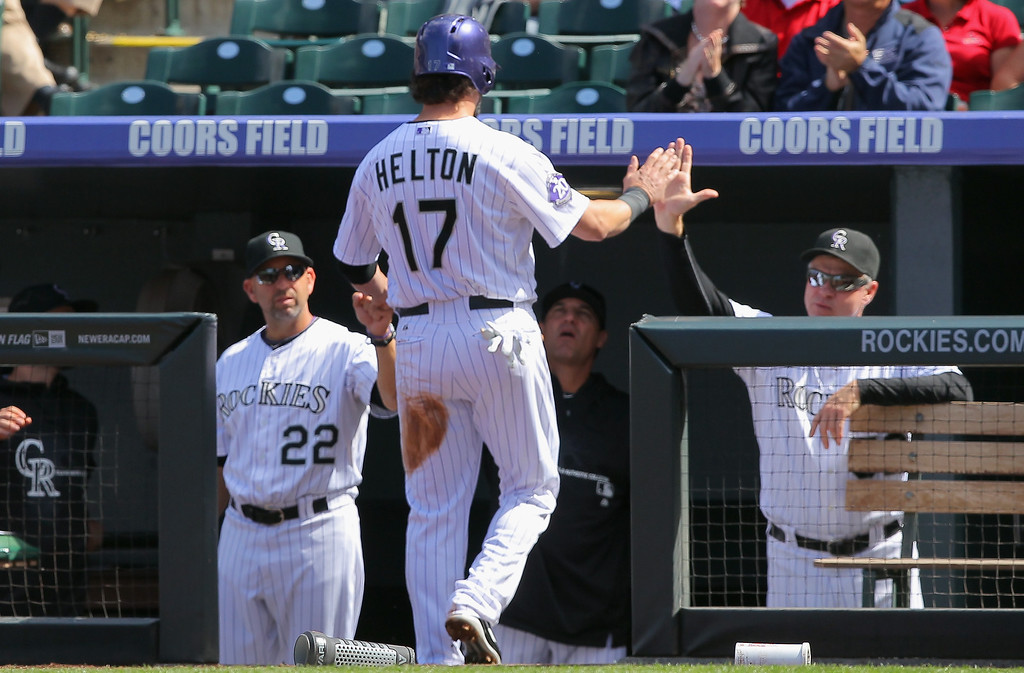 . Todd Helton #17 of the Colorado Rockies is welcomed back to the dugout by manager manager Walt Weiss #22 and pitching coach pitching coach Jim Wright #52 after he scored against the St. Louis Cardinals the give the Rockies a 1-0 lead in the second inning at Coors Field on September 19, 2013 in Denver, Colorado.  (Photo by Doug Pensinger/Getty Images)
