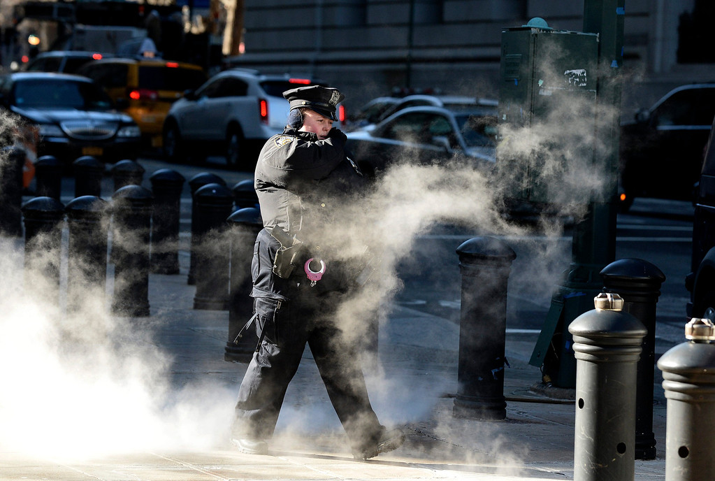 . A police officer walks past a steam grate in Lower Manhattan Borough of New York, New York, USA, 07 January 2013. Many parts of the United States are experiencing record cold temperatures due to an usual polar vortex of arctic air.  EPA/ANDREW GOMBERT