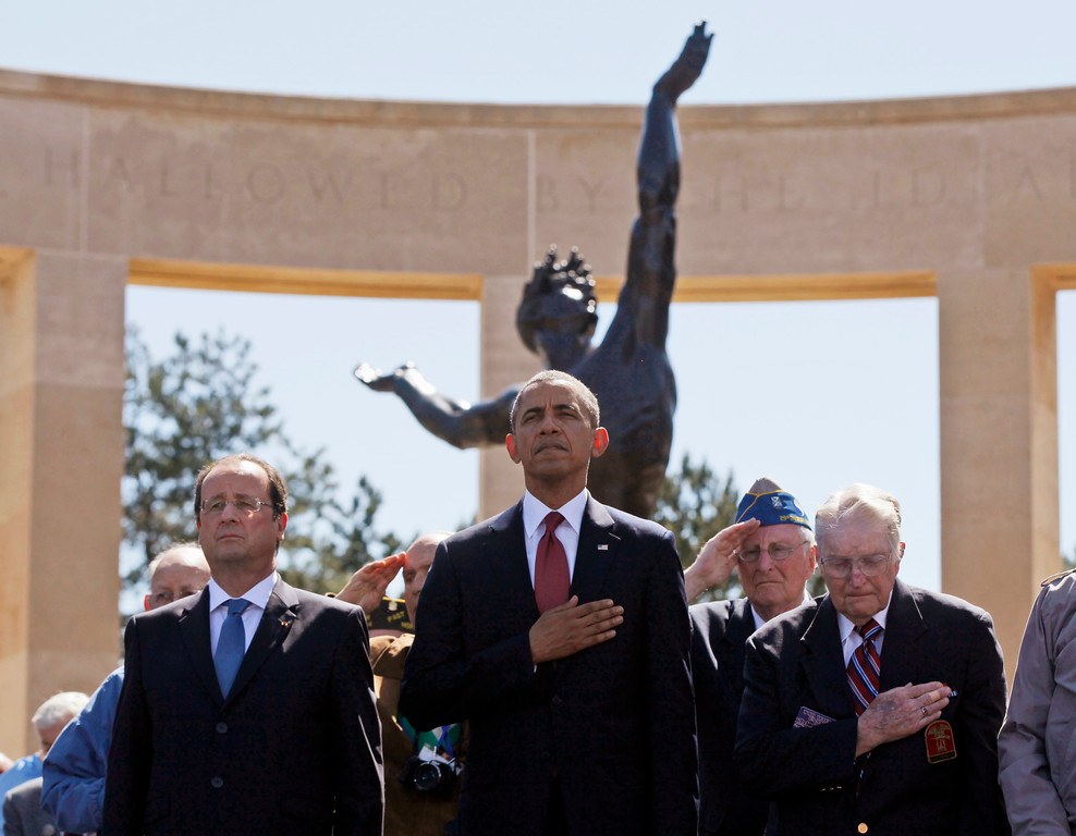 . U.S. President Barack Obama, centre, and French President Francois Hollande, left,  stand with veterans during the playing of Taps, at Normandy American Cemetery at Omaha Beach as he participates in the 70th anniversary of D-Day in Colleville sur Mer, Normandy, France, Friday, June 6, 2014. (AP Photo/Charles Dharapak)