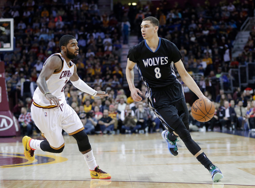 . Minnesota Timberwolves\' Zach LaVine (8) drives on Cleveland Cavaliers\' Kyrie Irving in the third quarter of an NBA basketball game Tuesday, Dec. 23, 2014, in Cleveland. (AP Photo/Mark Duncan)