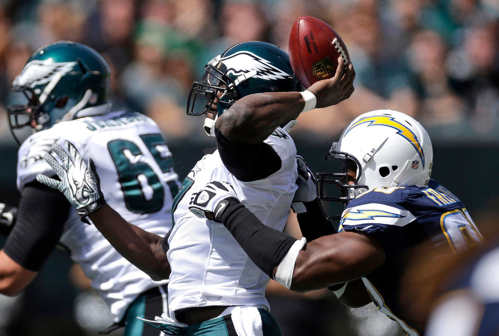. Philadelphia Eagles\' Michael Vick, left, tries to pass as he is hit from behind by San Diego Chargers\' Dwight Freeney during the first half of an NFL football game, Sunday, Sept. 15, 2013, in Philadelphia. (AP Photo/Matt Rourke)