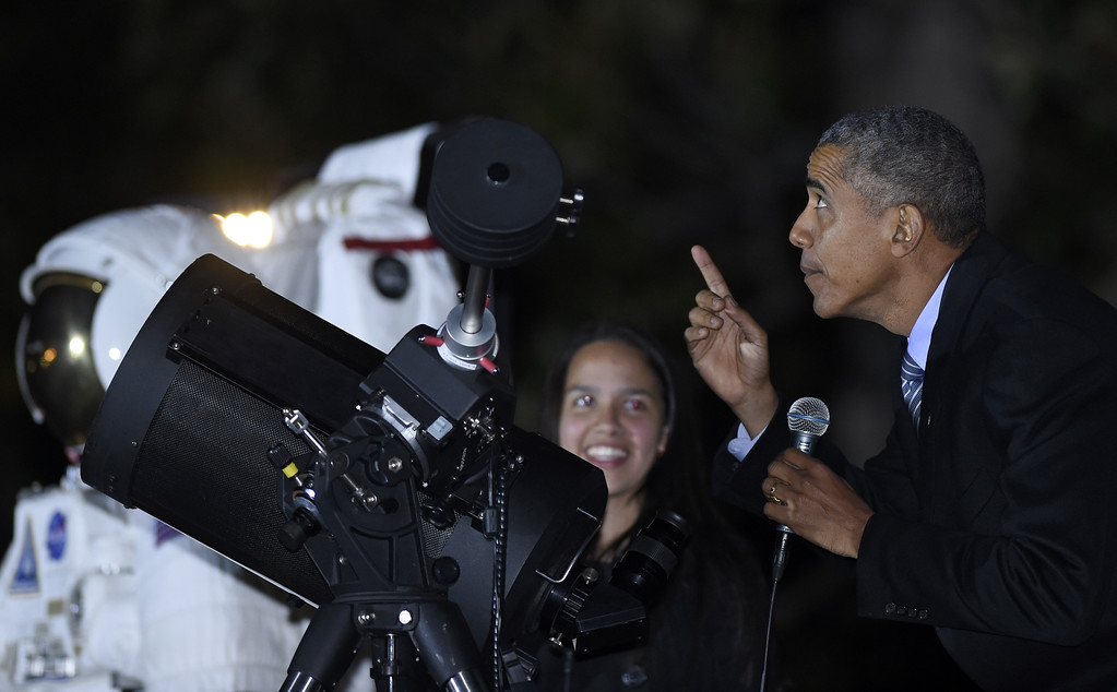. President Barack Obama, right, looks up at the moon as he talks with Agatha Sofia Alvarez-Bareiro, left, a high school senior from the Brooklyn borough of New York as Obama prepares to look at the moon at the second-ever White House Astronomy Night on the South Lawn of the White House in Washington, Monday, Oct. 19, 2015. The event brings together students, teachers, astronomers, engineers, scientists, and space enthusiasts for an evening of stargazing. (AP Photo/Susan Walsh)