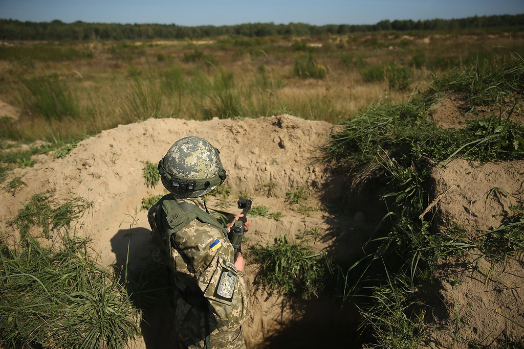 ". A Ukrainian marine stands in a trench during training on the second day of the ""Rapid Trident\"" NATO military exercises on September 16, 2014 near Yavorov, Ukraine.  (Photo by Sean Gallup/Getty Images)"