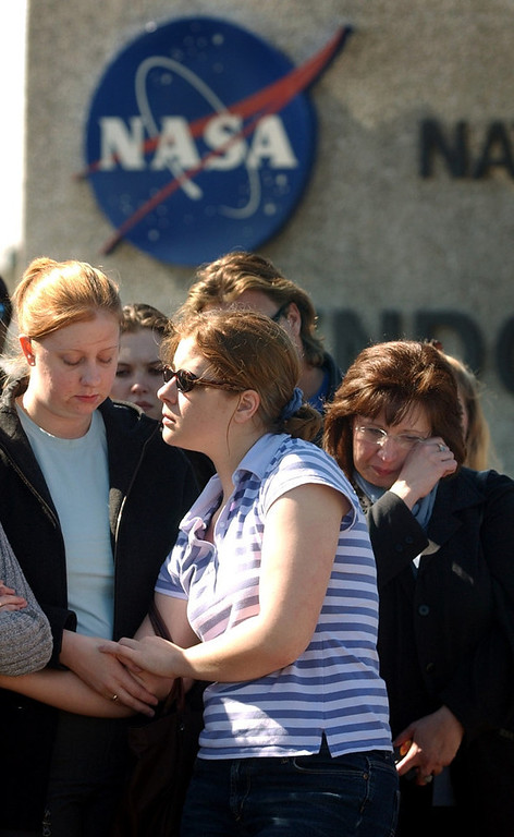 . Kerri Gauthier,21,  (left) comforts her sister Kristin Gauthier, 18, both of Houston as they listen via radio to the memorial service for space shuttle Columbia astronauts going on with President Bush inside the center on Tuesday, February 4, 2003. At right,  Char Rogers of Houston wipes  a tear. They were all outside the gates to the center. CYRUS MCCRIMMON, The Denver Post