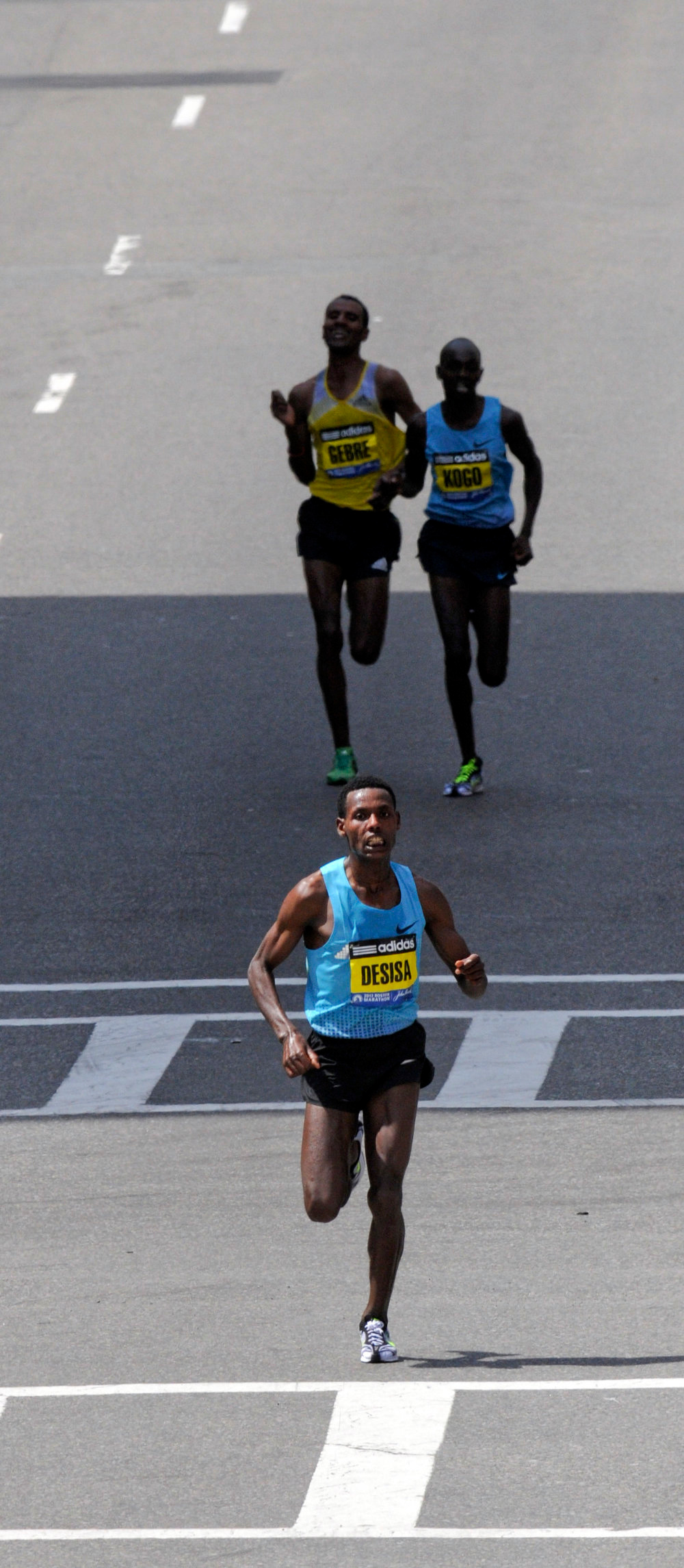 """. Lelisa Desisa Benti of Ethiopia (front) runs a few seconds ahead of Micah Kogo of Kenya and Gebregziabher \""""Gebre\"""" Gebremariam of Ethiopa as they sprint to the finish of the men\'s division of the 117th Boston Marathon in Boston, Massachusetts April 15, 2013. REUTERS/Neal Hamberg"""