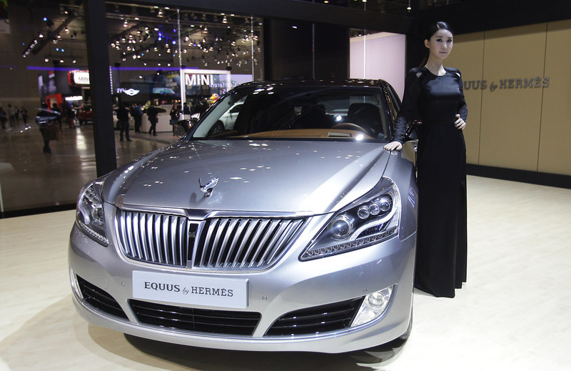 . A Model poses next to a Hyundai Equus Hermes at the Seoul Motor Show 2013 on March 28, 2013 in Goyang, South Korea. The Seoul Motor Show 2013 will be held in March 29-April 7, featuring state-of-the-art technologies and concept cars from global automakers. The show is its ninth since the first one was held in 1995. About 384 companies from 14 countries, including auto parts manufacturers and tire makers, will set up booths to showcase trends in their respective industries, and to promote their latest products during the show.  (Photo by Chung Sung-Jun/Getty Images)