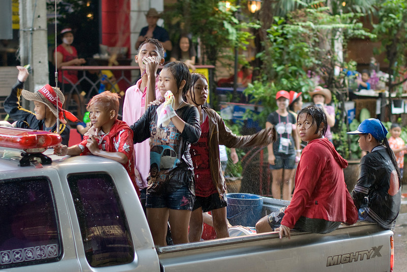 Kids getting a shot of water from back of truck in Thailand's Songkran Festival