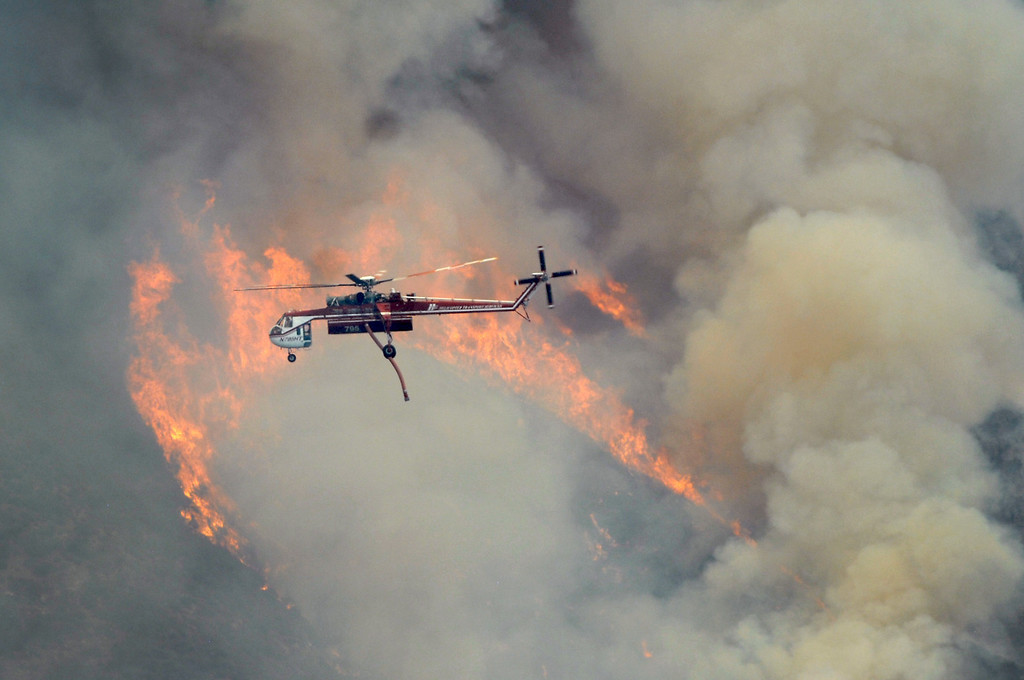 . A fire helicopter files past flames in Ventura County, Friday, May 3, 2013. (Michael Owen Baker/Los Angeles Daily News)