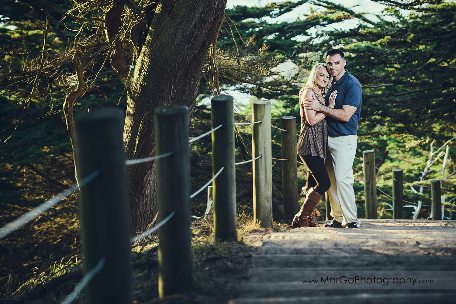 man in navy blue shirt and woman in brown tunic on the wooden stairs looking into camera during engagement session at San Francisco Lands End