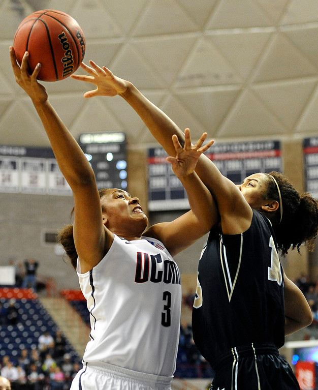 . Connecticut\'s Morgan Tuck, left, goes up for a basket while guarded by Idaho\'s Ali Forde, right, during the first half of a first-round game in the women\'s NCAA college basketball tournament in Storrs, Conn., Saturday, March 23, 2013. Connecticut won 105-37. (AP Photo/Jessica Hill)