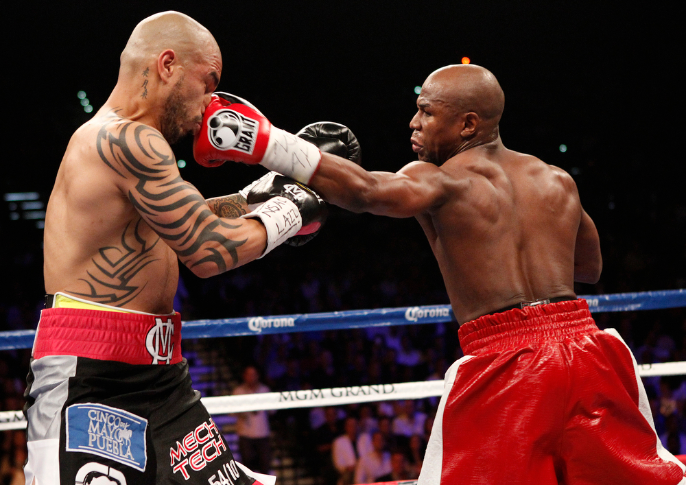 . Floyd Mayweather Jr. hits Miguel Cotto during their WBA Super Welterweight title bout at the MGM Grand in Las Vegas Saturday, May 5, 2012. (AP Photo/Las Vegas Review-Journal, John Locher)