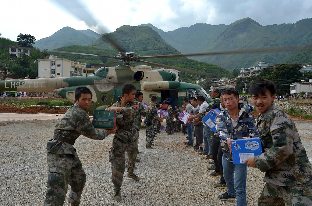 . Rescue workers and volunteers deliver suppliers transported by a helicopter to the town of Longtoushan in Ludian county in southwest China\'s Yunnan province Tuesday, Aug. 5, 2014.  (AP Photo)